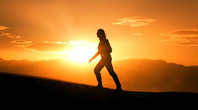 stock-footage-lone-female-hiker-in-silhouette-walking-over-sand-dunes-into-the-sun-in-a-desert-environment